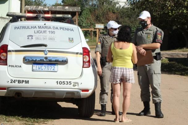 Ao lado de uma viatura da Patrulha Maria da Penha, dois policiais militares (uma mulher e um homem) conversam com uma mulher que aparece de costas em uma rua de chão batido.