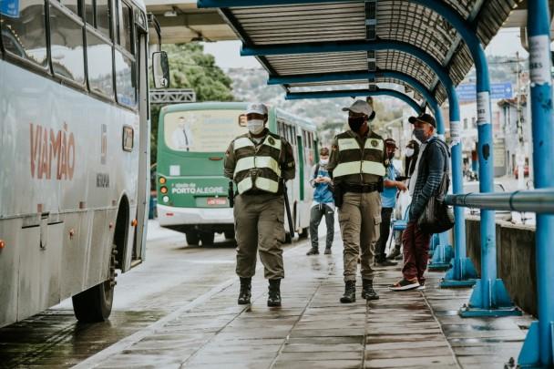 Um casal de PMs fardados caminha em uma parada de ônibus onde pessoas aguardam. Na via ao lado, passam dois coletivos, um verde, de Porto Alegre, e outro azul, de Viamão.