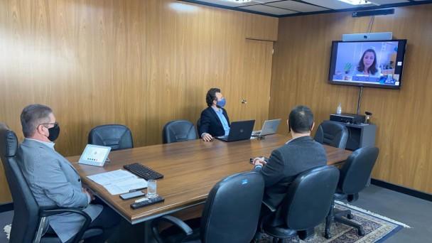 Vice-governador sentado diante da ponta de grande mesa de reunião em seu gabinete. Secretário-executivo do RS Seguro, Antônio Padilha, sentado ao lado esquerdo da mesa. Na outra ponta, TV com imagem da videoconferência de do projeto de proteção à mulher.