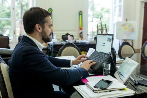 Sentado diante da mesa de trabalho em seu gabinete, o governador Eduardo Leite digita em um notebook a sua frente. Neste momento, ele assinou digitalmente o decreto que cria o Comitê Interinstitucional de Enfrentamento à Violência Contra a Mulher.