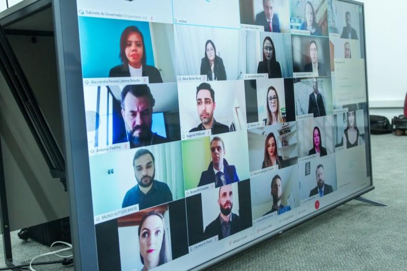 A imagem mostra um  telão dividido em várias imagens dos formandos e familiares que acompanhavam a formatura por videoconferência