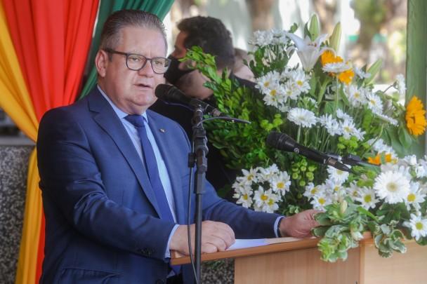 De terno e gravata, em pé, diante de um púlpito com microfone e um arranjo de flores, o vice-governador Ranolfo Vieira Júnior. Ao fundo, cortina com as cores da bandeira do RS.