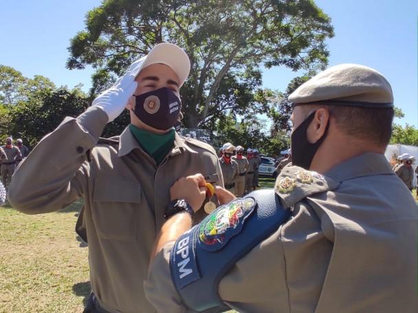 Soldado Bruno Alfama Lopes presta continência enquanto o comandante do CRPO Vale do Rio Pardo, coronel Valmir José dos Reis, lhe afixa ao peito medalha pela primeira colocação no curso de formação.