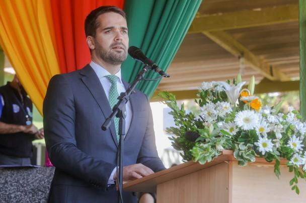De terno e gravata, em pé diante de um púlpito com microfone, o governador Eduardo Leite. Ao lado, arranjo de flores, Ao fundo, cortina com as cores da bandeira do RS.